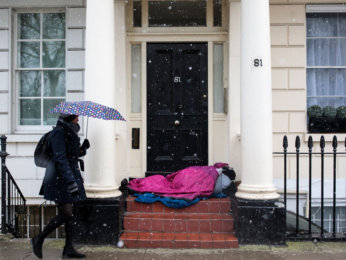 A-woman-carrying-an-umbrella-walks-past-a-homeless-person-sleeping-in-a-doorway-during-a-snow-shower-on-February-26